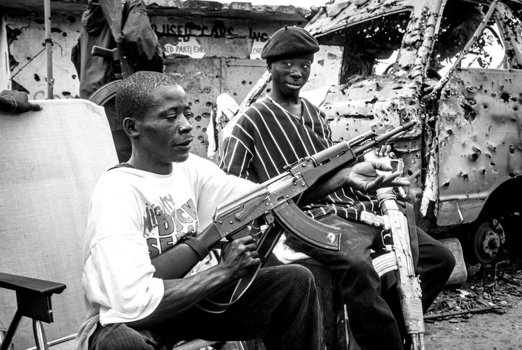 2003, Monrovia during civil war. Lurd rebels had just taken most of the city by force. Charles Taylor wanted to stay in power and both sides used child soldiers to defend their territory. 15 Years Ago AK47 Civil War EyeEm Documentary The Week on EyeEm Warzone Photography Blackandwhite Civil Disturbance Documentaryphotography Liberia Lord Of War Monochrome Monrovia Reportage Streetphotography Warzone