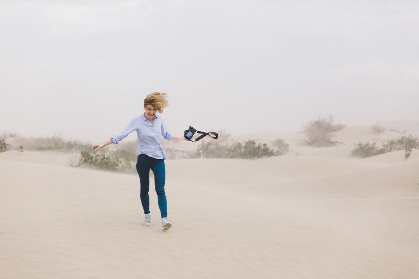 Arid Climate Arid Landscape Blond Hair Clear Sky Curly Hair Day Death Valley Death Valley National Park Desert Dunes Full Length Girl Leisure Activity Motion Nature One Person One Woman Only Only Women Outdoors Sand Dune Sand Storm Sky Storm Young Adult Young Women