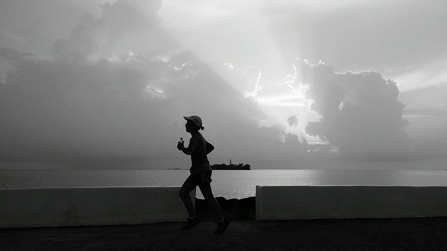 Side View Full Length Of Man Jogging By Sea On Footpath Against Sky