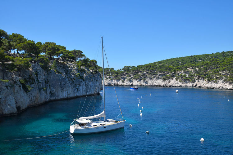 White sea yacht in rocky calanque of Cassis, France Nautical Vessel Water Transportation Mode Of Transportation Blue Sailboat Sky Sea Clear Sky Nature Day Beauty In Nature Sailing Yacht Outdoors Yachting Luxury Anchored Moored Mast Calanques  Calanque Summer Vacations Travel Destinations