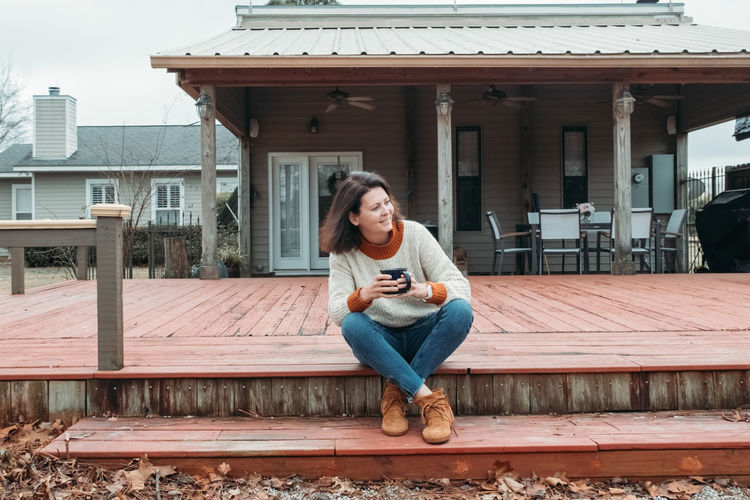 Full length of woman holding coffee cup while sitting on steps outdoors