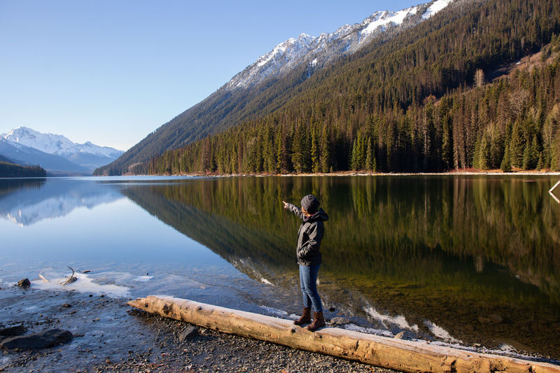 Side view of young woman walking on log at lakeshore against mountain