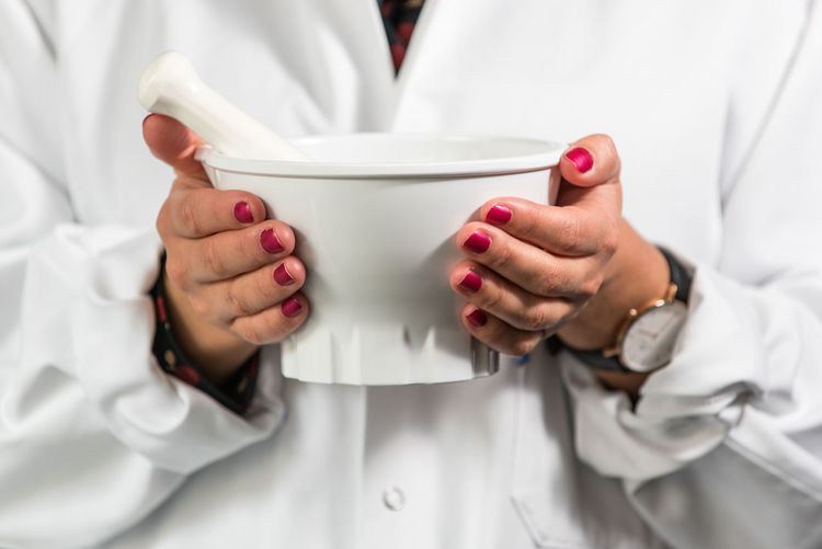 Midsection of doctor holding mortar and pestle