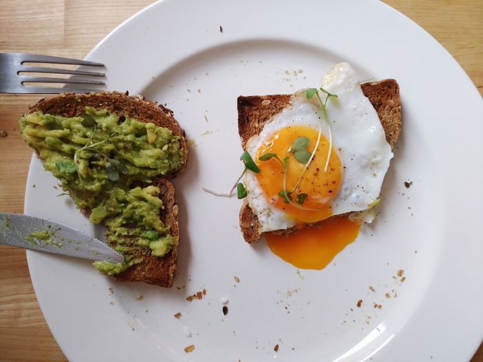 Indoors  Plate Food And Drink Food High Angle View Bread Healthy Eating Freshness No People Ready-to-eat Close-up Egg Yolk DaySandwich Toasted Bread Fried Egg Wood - Material Table Directly Above Egg Food And Drink Avocado Eating Lunch Eating Healthy