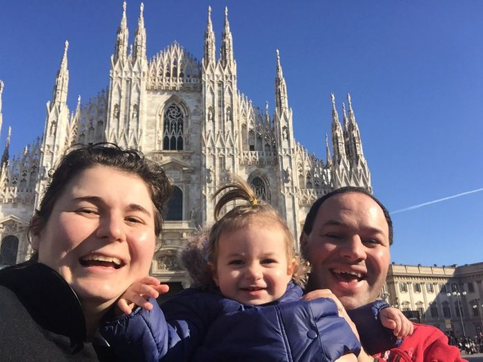Portrait of happy family standing against milan cathedral