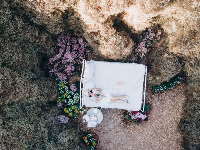 Drone shot of woman lying on bed amidst trees in forest