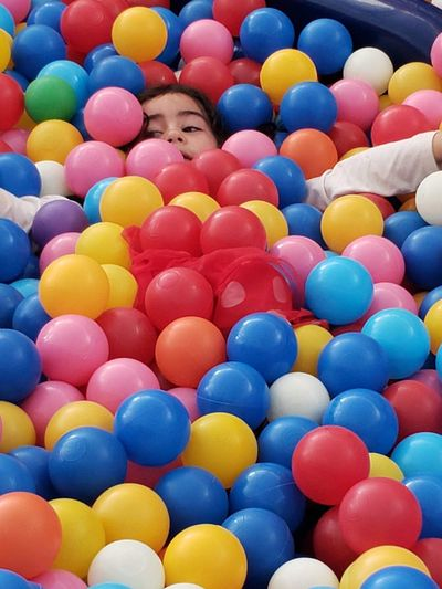 High angle view of cute girl in multi colored balls