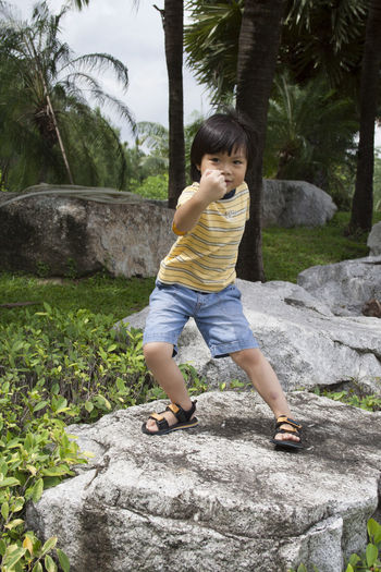 Full length of boy standing on rock