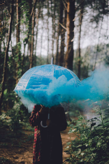 Woman With Umbrella And Blue Smoke Standing In Forest