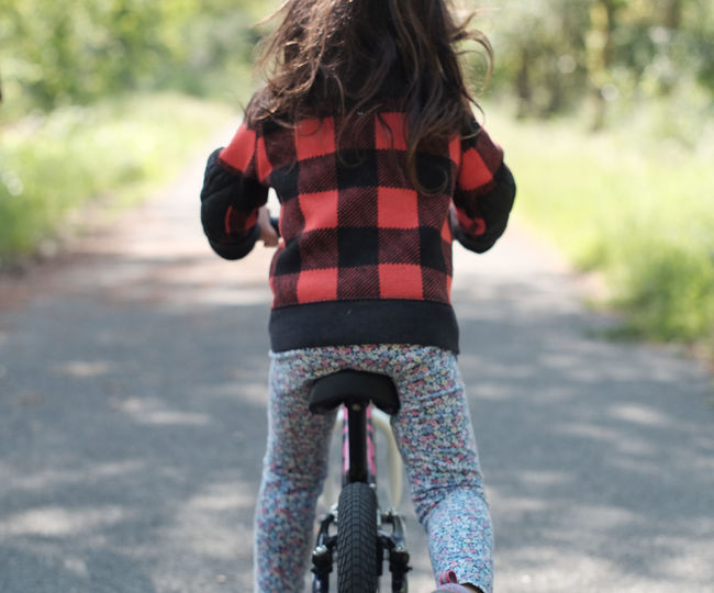 Rear View Of Girl On Bicycle