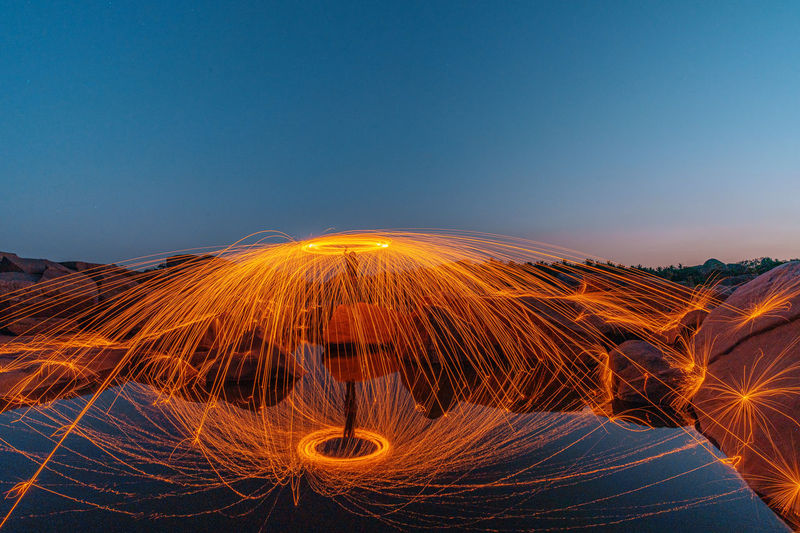 Reflection of man spinning wire wool on land in lake against clear sky at night