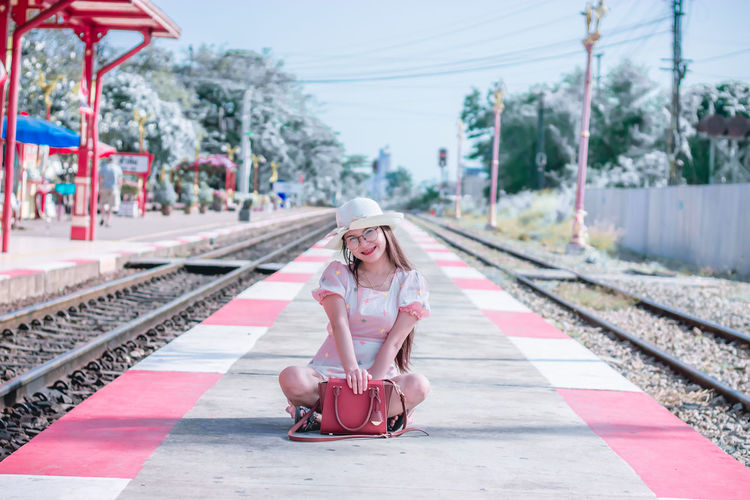 Full length portrait of woman at railroad station