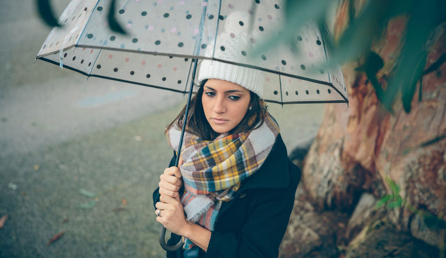 Portrait of young beautiful girl under a umbrella in an autumn rainy day Woman Cold Winter Hat Scarf Horizontal Rain Girl Young Female Outdoors Autumn Fall Real People Caucasian One Person Serious Solitude Pensive Coat Alone Relax Concentration Umbrella Rainy