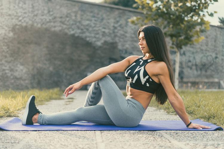 Full Length Of Woman Sitting On Exercise Mat