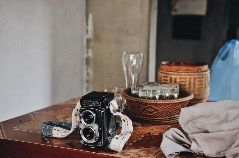 Camera - Photographic Equipment Camera Travel Destinations Freedom Backpack Food Street Photography Travel Laos Indoors  Table Technology No People Still Life Close-up Retro Styled Focus On Foreground Home Interior Food And Drink Food Freshness Photography Themes Arts Culture And Entertainment Luxury Day Candle Communication Wood - Material Camera - Photographic Equipment