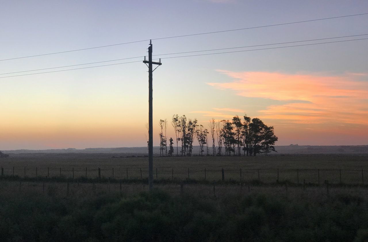 sky, sunset, cable, electricity, landscape, land, tranquil scene, field, tranquility, environment, beauty in nature, technology, scenics - nature, power line, nature, no people, orange color, plant, electricity pylon, power supply, sun, outdoors, telephone line