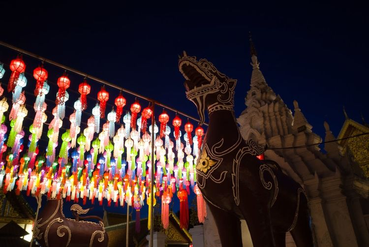 Low angle view of illuminated sculptures against sky at night