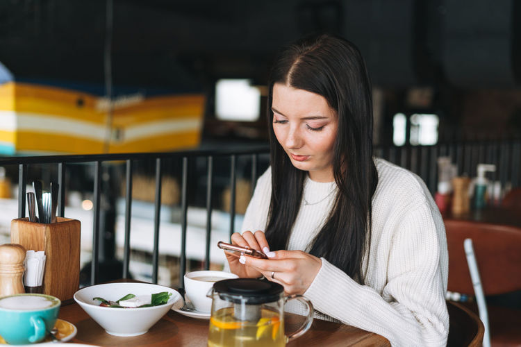 Attractive young brunette smiling woman in casual using mobile phone having brunch in cafe