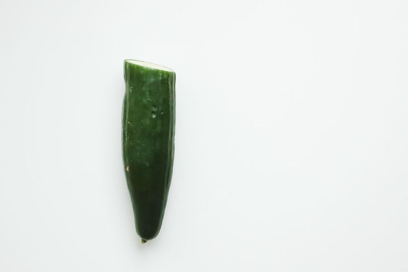 Close-up of green chili over white background