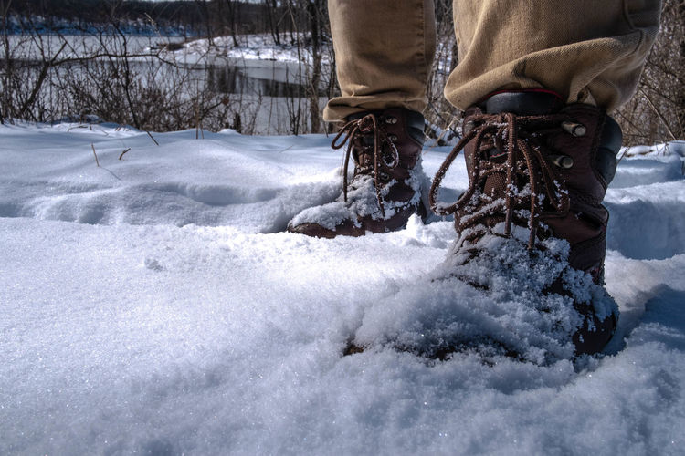 Low section of man wearing shoes standing on snow covered field