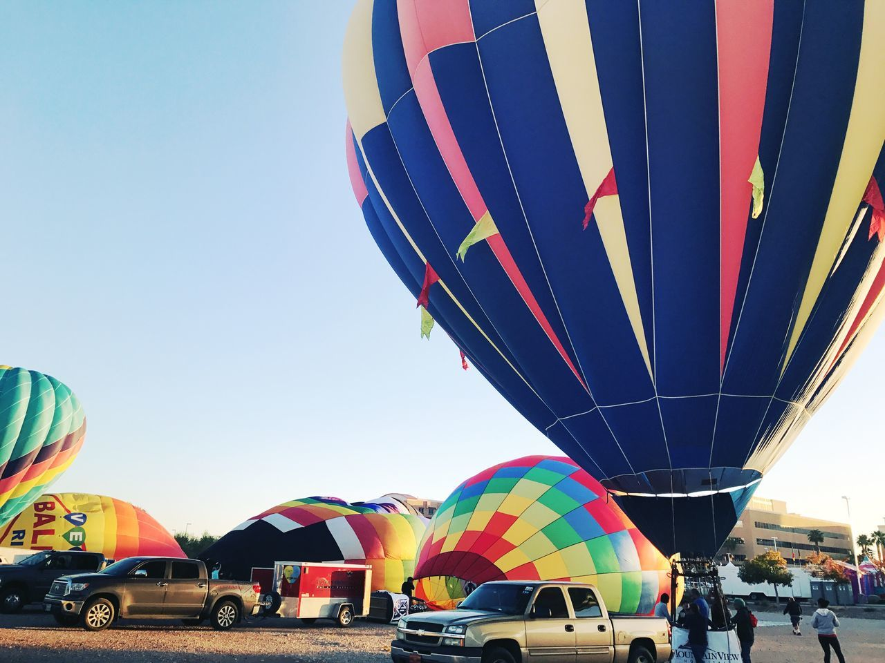 multi colored, hot air balloon, transportation, mode of transport, ballooning festival, outdoors, clear sky, sky, day, city, no people