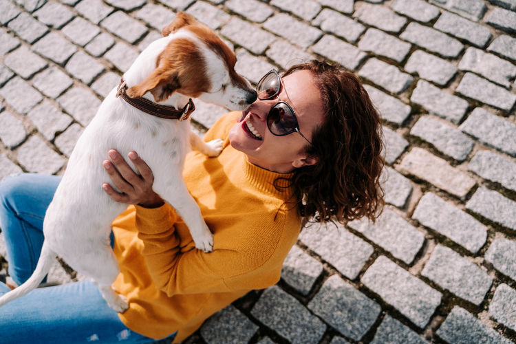 High angle view of woman embracing with dog sitting street