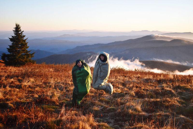 Friends sunrise sleeping bag jump on field against mountain range