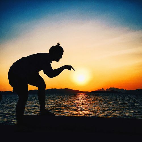 Optical illusion of silhouette man touching sun at beach against sky during sunset