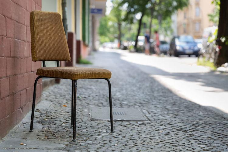 Empty Chair On Sidewalk By Brick Wall