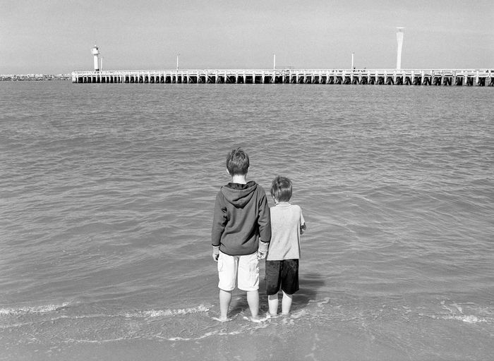 Rear View Of Brothers Standing On Shore Against Pier Over Sea