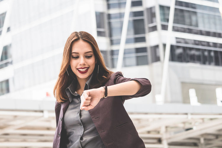 Smiling young businesswoman checking time while standing on elevated walkway