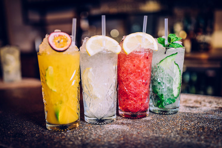 Close-up of drinks served in glasses on marble