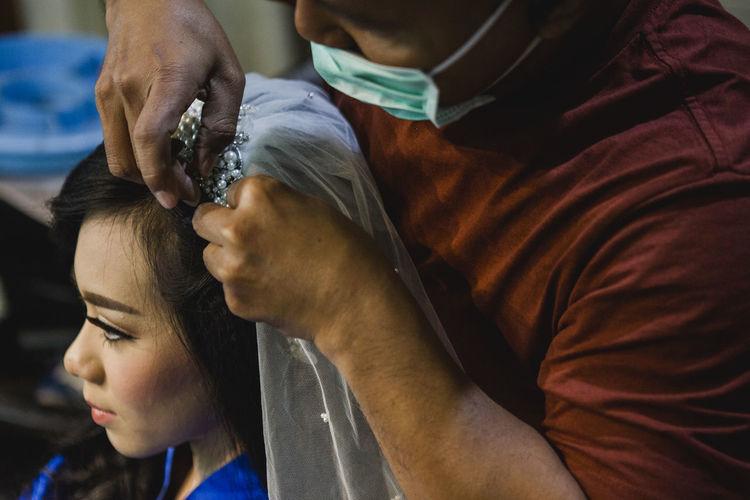Hairdresser adjusting veil of bride