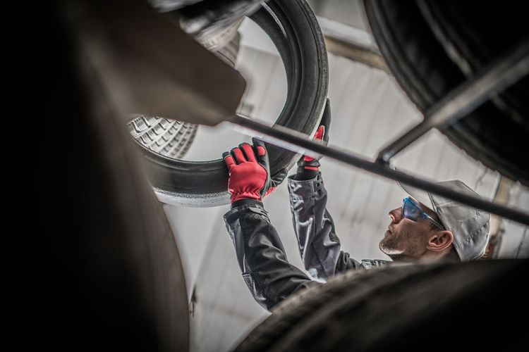 Low angle view of mechanic working while holding tire in garage