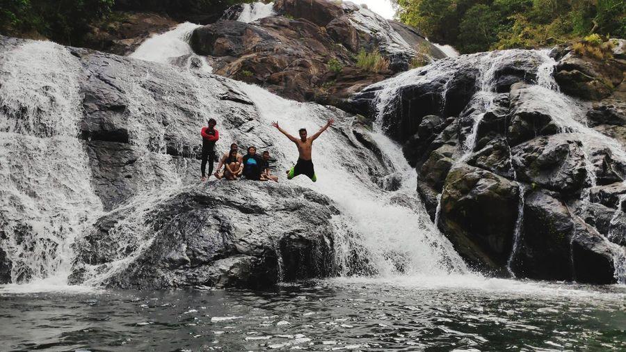 People on rocks by waterfall
