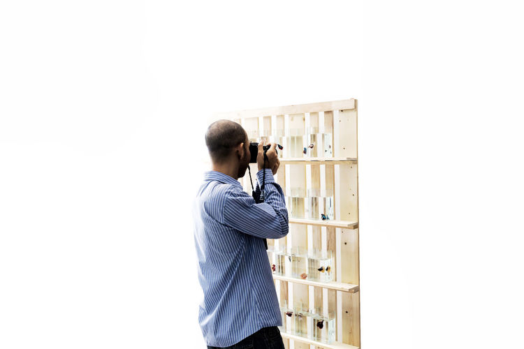 Side View Of Man Photographing Fish Tanks On Shelves Against White Background