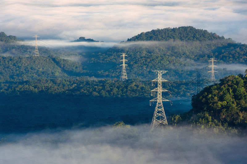 Morning smooth fog. energy and environment concept. high voltage power poles.
