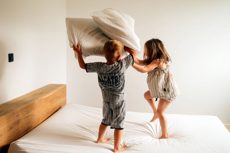 Two kids at home having a good time playing pillow fight on parents bed on morning daylight