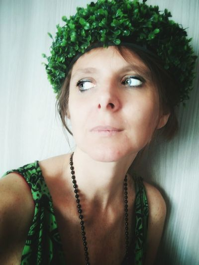 Close-up of woman looking away while wearing wreath at home