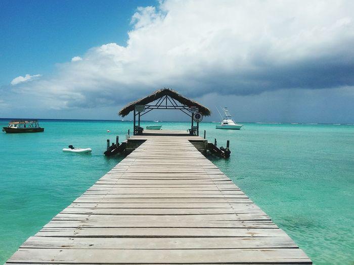 Gazebo on pier over sea against cloudy sky