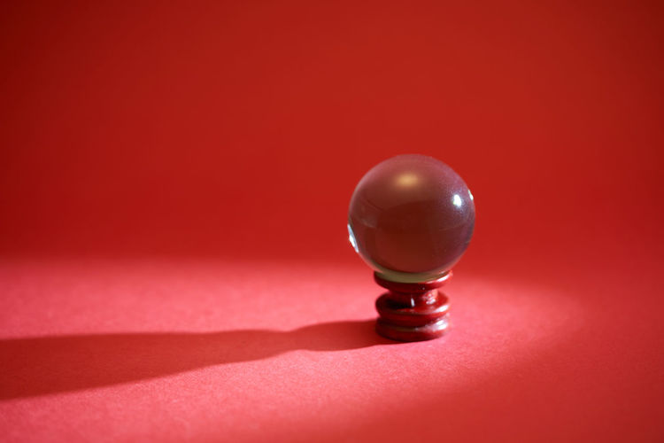 Close-up of crystal ball on red table