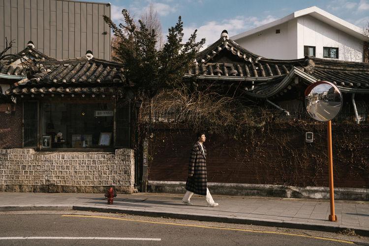Man walking on street against buildings