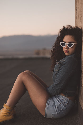 Portrait Of Woman In Sunglasses Sitting Outdoors