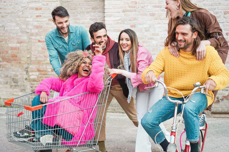 Happy friends having fun with shopping kart and vintage bicycle Millennials Millenials Young People Friends Party Group Of People Young Adult Smiling Togetherness Happiness Men Young Men Young Women Friendship Emotion Shopping
