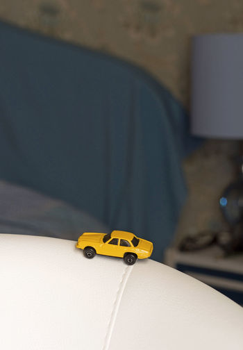 Close-up of yellow toy car on sofa at home