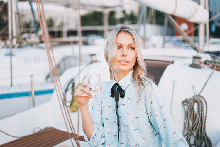Beautiful blonde young woman in blue dress with glass of soda on boat at pier in sunset time