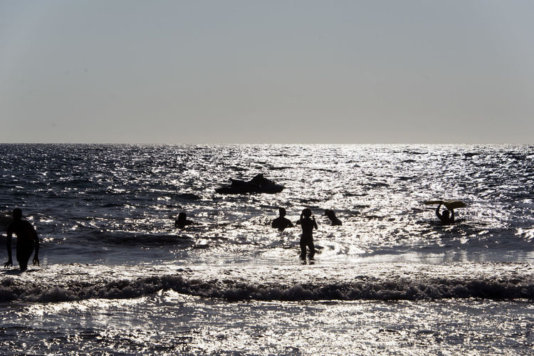 SILHOUETTE OF People playing, swimming in the waves in the island of Patmos, Greece in summer time Beach Beauty In Nature Day Group Of People Horizon Horizon Over Water Land Leisure Activity Lifestyles Men Motion Nature Outdoors People Real People Sea Silhouette Sky Water Wave