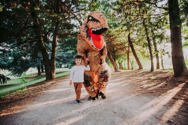 Boy walking with person wearing dinosaur costume in park