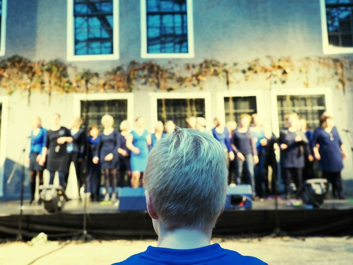 Rear View Of Boy Looking At Choir Performance