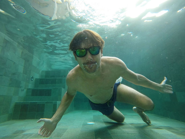 Young, happy man with sunglasses in the pool Water Swimming Underwater Leisure Activity Lifestyles Eyewear Swimming Pool Men Happy Thailand Pool Sun Fun Vacations Destination Handsome Young Man Sun Glasses Vitality Cool Hipster Relaxing Travel Hotel